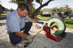 A plumber in Brea snakes a power auger down a drain